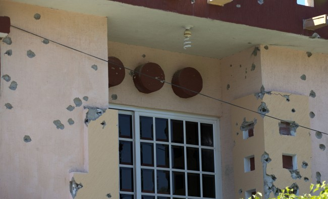 A house is riddled with bullet holes after clashes between the Self-Defense Council of Michoacan, (CAM), and members of the Knights Templar drug cartel a day earlier in Nueva Italia, Mexico, Monday, Jan. 13, 2014. A day earlier the self-defenses encountered resistance as they tried to rid the town of the Knights Templar drug cartel while the government announced today that federal forces will take over security in a large swath of a western Mexico that has been hard hit by violence. (AP Photo/Eduardo Verdugo)