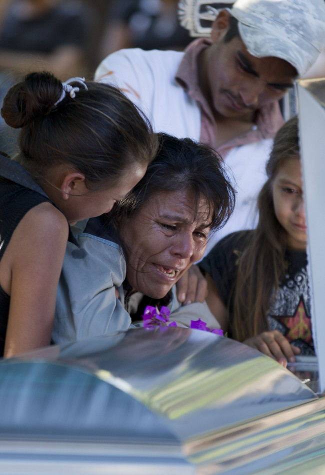 Juana Perez cri­es besides the coffin of his son Rodrigo Benitez, 2, killed in the recent fighting