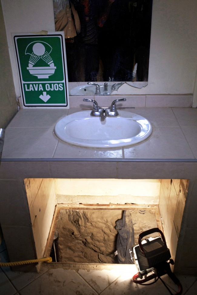 his July 12, 2012 file photo shows the entrance to a cross border illegal tunnel lit by a lamp after it was found underneath a bathroom sink by the Mexican army inside a warehouse in Tijuana, Mexico. More than 75 such underground passages have been found along the border since 2008, concentrated largely in California and Arizona. The job of searching these networks can be dangerous, so the U.S. Border Patrol is unveiling its latest technology in the underground war, a wireless, camera-equipped robot that can do the job in a fraction of the time. (AP Photo/Alejandro Cossio)