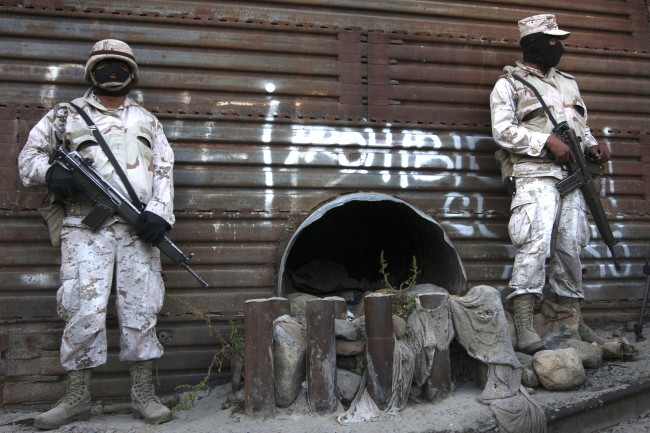 This June 4, 2010 file photo shows Mexican army soldiers standing guard next to a tunnel at the border wall in Tijuana, Mexico. More than 75 such underground passages have been found along the border since 2008, concentrated largely in California and Arizona. The job of searching these networks can be dangerous, so the U.S. Border Patrol is unveiling its latest technology in the underground war, a wireless, camera-equipped robot that can do the job in a fraction of the time. (AP Photo,File)