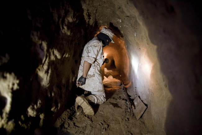 This Nov. 4, 2010 file photo shows a Mexican Army soldier using a flashlight to shows reporters a tunnel connecting warehouses on either side of California's border with Mexico in Tijuana. More than 75 such underground passages have been found along the border since 2008, concentrated largely in California and Arizona. The job of searching these networks can be dangerous, so the U.S. Border Patrol is unveiling its latest technology in the underground war, a wireless, camera-equipped robot that can do the job in a fraction of the time. (AP Photo/Guillermo Arias)