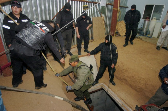 Soldiers use an elevator to descend journalists to a 9 meters deep (29 feet), 122 meters long (400 ft) tunnel found by the Army inside a house near the US-Mexico border in Tijuana, Mexico, Saturday, Nov. 7, 2009. Six suspects were arrested. (AP Photo/Guillermo Arias)