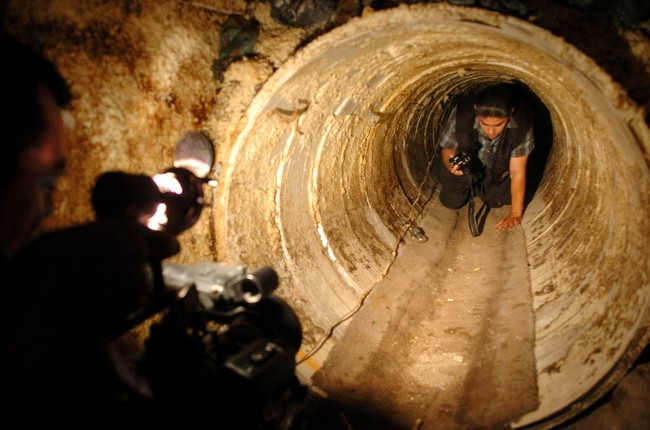 This July 8, 2004 file photo shows a Mexican federal agent crawls through a hidden tunnel, presumably used to transport drugs from Mexico to the U.S. The job of searching these networks can be dangerous, so the U.S. Border Patrol is unveiling its latest technology in the underground war, a wireless, camera-equipped robot that can do the job in a fraction of the time. (AP Photo/David Maung)
