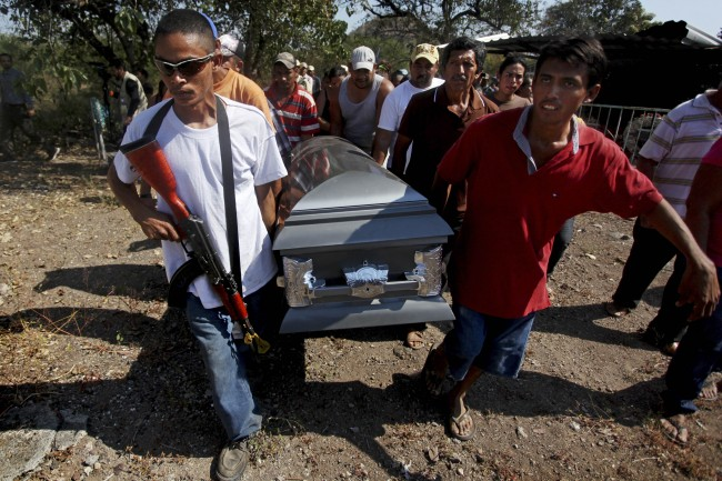 Men carry the coffin that contain the remains of Mario Perez as they prepare to bury him in Antunez, Mexico, Wednesday, Jan. 15, 2014. Perez was one of the three civilians killed a day earlier by federal forces after they tried to disarm men belonging to a self-defense group that is fighting to rid the Knights Templar drug cartel in a region of Michoacan state known as Tierra Caliente.