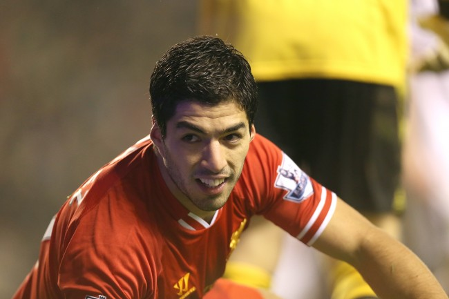Liverpool's Luis Suarez smiles after being brought down by Aston Villa goalkeeper Brad Guzan to earn his side a penalty