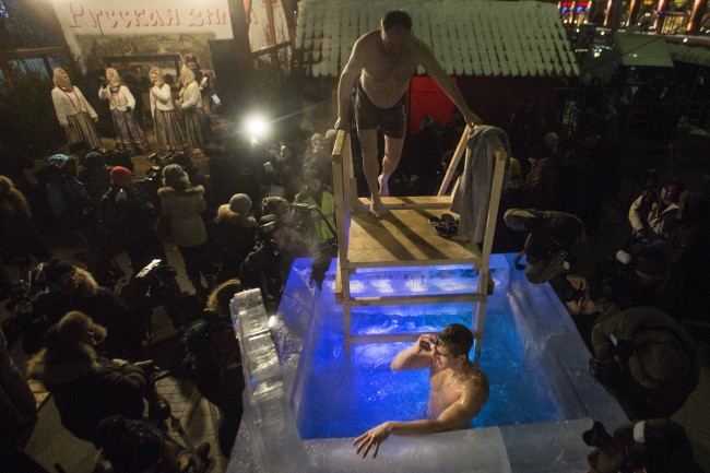 A man crosses himself in the ice cold water, as another waits his turn to plunge in a small ice pool to mark Epiphany in the center of Moscow, next to Red Square, Russia, late Saturday, Jan. 18, 2014.