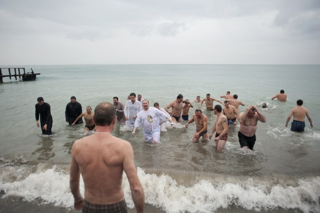 Orthodox priests and believers bath in the Black Sea during Epiphany celebrations in Khosta, Sochi district Sunday, Jan. 19, 2014. Thousands of Russian Orthodox Church followers will plunge into icy rivers and ponds across the country to mark Epiphany, cleansing themselves with water deemed holy for the day. (AP Photo/Lesya Polyakova)