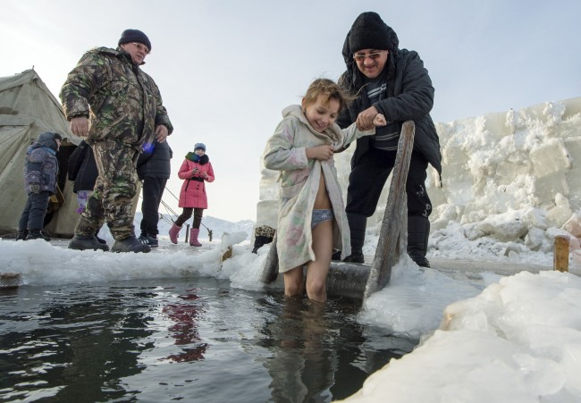 A girl smiles as she is helped to get into the ice-cold water of the Ob River after it was blessed by an Orthodox priest on Epiphany Sunday, Jan. 19, 2014 in Ordynka village near Novosibirsk about 2800 kilometers (1,750 miles) east of Moscow.