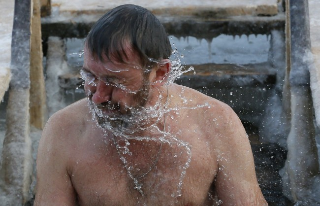 A Russian Orthodox believer swims in the icy water on Epiphany in the Neva River in St.Petersburg, Russia, Sunday, Jan. 19, 2014. The temperature in St.Petersburg is -16C