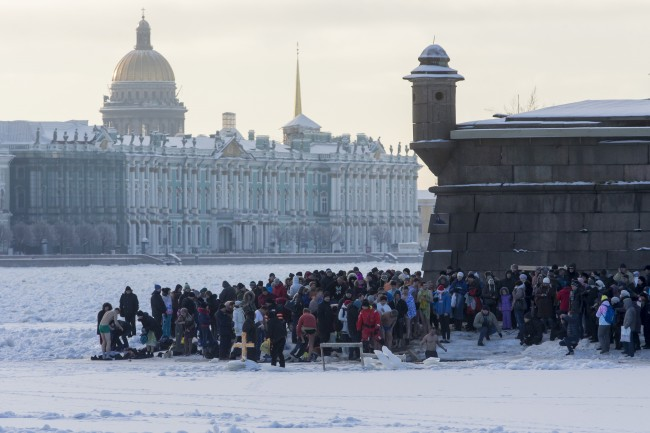 Russian Orthodox believers gather to swim in the icy water on Epiphany in the Neva River in St.Petersburg, Russia, Sunday, Jan. 19, 2014, with Zimny (Winter) Palace in the background.