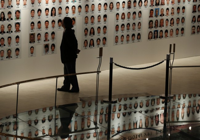 A visitor look at athletes' portraits before a launching ceremony for Japan national team members for the Sochi Winter Olympics at a hotel in Tokyo Monday, Jan. 20, 2014. Japan will send 99 athletes and 112 officials to Sochi. (AP Photo/Shizuo Kambayashi)