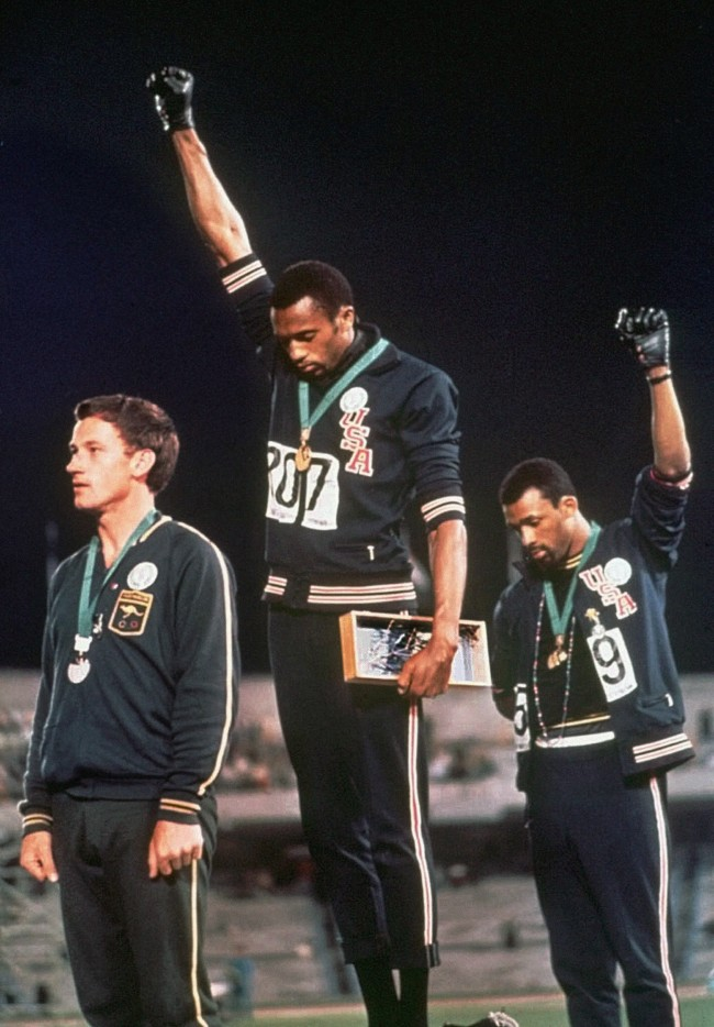 Extending gloved hands skyward in racial protest, U.S. athletes Tommie Smith, center, and John Carlos stare downward during the playing of the Star Spangled Banner after Smith received the gold and Carlos the bronze for the 200 meter run at the Summer Olympic Games in Mexico City on Oct. 16, 1968. Australian silver medalist Peter Norman is at left. (AP Photo/files)