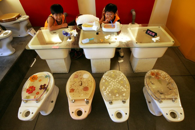 Young Taiwanese children sit on western style toilets as they enjoy ice-cream served in a miniature Asian squat toilets at Marton, Taiwan's most recent hit theme restaurant, (named after the Chinese word Matong, meaning toilet), Sunday, May 29, 2005, in Taiwan's southern port city of Khaohsiung. The restaurant's toilet theme has become so popular serving light meals and ice-cream treats in western and Asian style toilets, the owner Eric Wang, 26, has opened a second branch just seven months after the first. (AP Photo/Wally Santana)