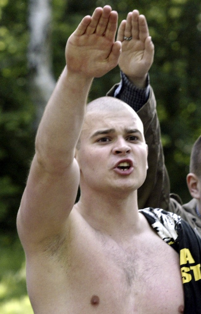 "Maxim Martsinkevich, also known as ""The Hatchet"" in Russian, gives the Nazi salute during a gathering of skinheads outside Moscow, in this June 16, 2004, file photo. A Moscow court sanctioned the arrest of Martsinkevich for his role as a leader in a right-wing ultrtanationalist group, the RIA-Novosti news agency reported on Wednesday, July 4, 2007. Russia has seen a spike in racist and anti-immigrant violence in recent years."