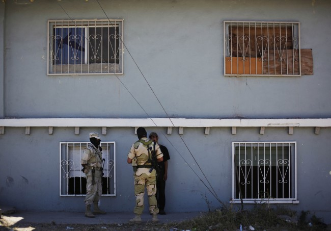 Soldiers talk to a suspect outside the house were the army found a tunnel under construction 40 yards from the border with the US in Tijuana, Mexico, Wednesday, July 8, 2009. (AP Photo/Guillermo Arias)