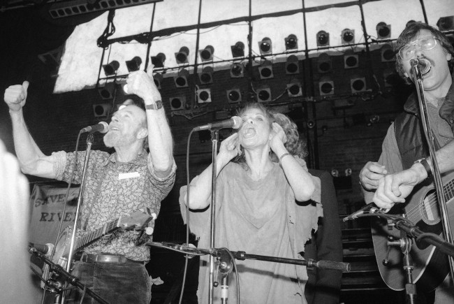 "Singer Pete Seeger, left, and Carly Simon sing an ecology ""protest"" song during a benefit to save the nation's rivers and streams from industrial pollution and natural erosion, on Monday, Feb. 1, 1983 at New York's Studio 54. (AP Photo/Nancy Kaye)"