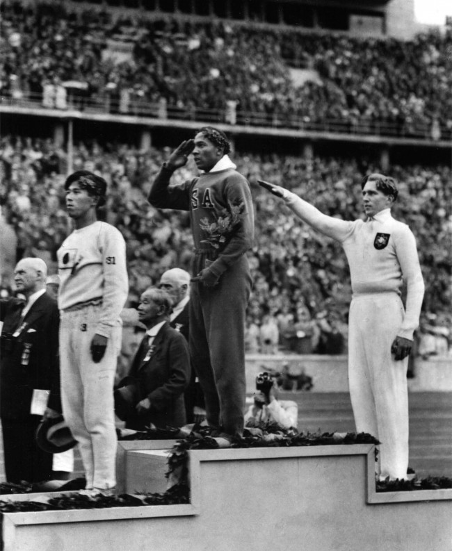 his Aug. 11, 1936 file photo shows America's Jesse Owens, center, salutes during the presentation of his gold medal for the long jump, after defeating Nazi Germany's Lutz Long, right, during the 1936 Summer Olympics in Berlin. Naoto Tajima of Japan, left, placed third. The performance of Jesse Owens will be honored in the stadium where he won four gold medals at the 1936 Olympic Games when the world championships are held in Berlin this month. (AP Photo/File)