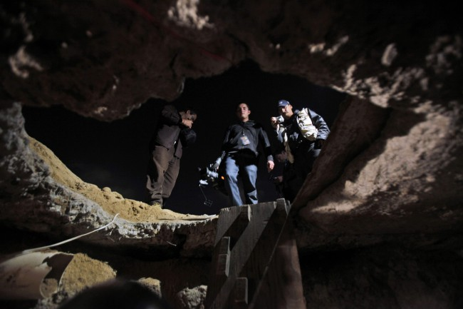 Members of the media stand outside a tunnel near the US-Mexico border in Tijuana, in Mexico, Tuesday, Oct. 27, 2009. Mexican soldiers have discovered a secret tunnel complete with electricity and an air supply that may have been planned for smuggling migrants or drugs under the U.S. border into San Diego (AP Photo/Guillermo Arias)