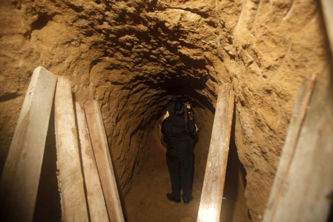 A cameraman takes footage inside a tunnel near the US-Mexico border in Tijuana, Mexico, Tuesday, Oct. 27, 2009. Mexican soldiers have discovered a secret tunnel complete with electricity and an air supply that may have been planned for smuggling migrants or drugs under the U.S. border into San Diego (AP Photo/Guillermo Arias)