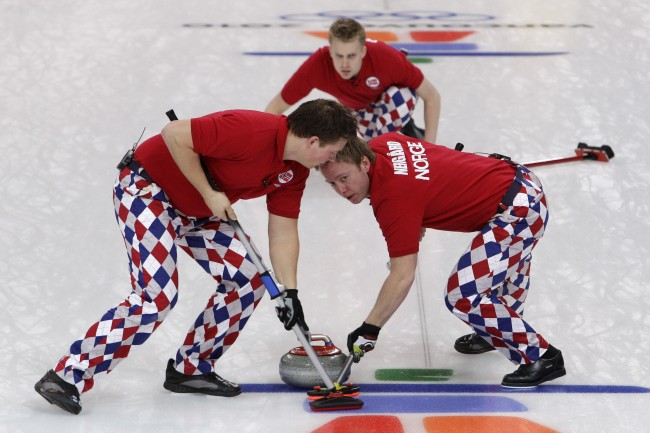 Norway's Christoffer Svae, left, and Torger Nergaard, sweep a stone delivered by Haavard Vad Petersson, top, in a win over China in men's curling at the Vancouver 2010 Olympics in Vancouver, British Columbia, Friday, Feb. 19, 2010. (AP Photo/Robert F. Bukaty)