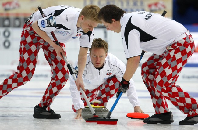 Norway's skip Torger Nergard throws his rock as first Havard Vad Petersson, left, and second Christoffer Svae sweep during a match against Sweden, at the Curling World Championships, in Cortina D'Ampezzo, Italy, Sunday, April 4, 2010. (AP Photo/Antonio Calanni)