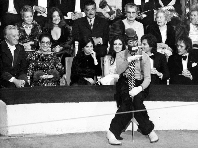 American comedian Jerry Lewis performs as a clown at the 38th Gala de L'Union des Artistes at the Cirque d'Hiver in Paris, France, April 24, 1971. Watching in the background are, from left, Italian film director and producer Vittorio de Sicca, opera singer Maria Callas, unidentified woman, Italian actress Gigliola Cinmetti and French singer Hughes Aufray.