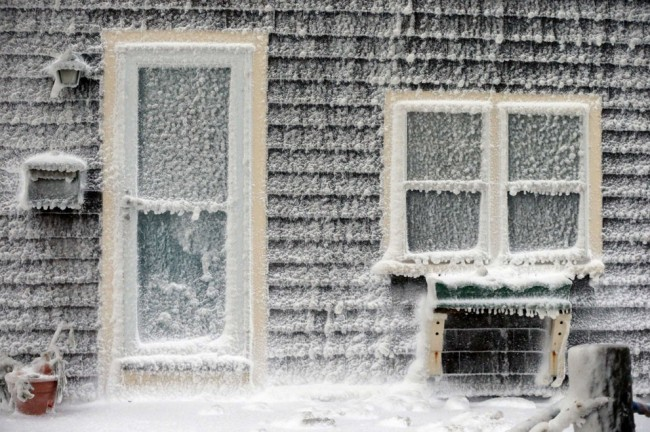Ice from breaking waves coats a house along the shore in Scituate, Massachusetts, on January 3, 2014. A winter storm slammed into the U.S. Northeast with howling winds and frigid cold, dumping nearly 2 feet (60 centimeters) of snow in some parts and whipping up blizzard-like conditions. (AP Photo/Michael Dwyer)