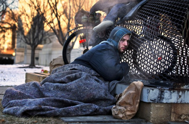 Nicholas Simmons, 20, of Greece, New York, warms himself on a steam grate with three homeless men by the Federal Trade Commission, just blocks from the Capitol, during frigid temperatures in Washington, D.C., on January 4, 2014. On New Year's Day, Simmons disappeared from his parents' house in a small upstate New York town, leaving behind his wallet, cellphone and everything else. Four days later, an Associated Press photographer, looking for a way to illustrate unusually cold weather, took his picture as he warmed himself on a steam grate a few blocks from the U.S. Capitol. His parents Paul and Michelle Simmons saw the photograph in USA Today Sunday morning after it was brought to their attention through a Facebook page set up to help find their son, according to police and family friends. They were able to report his location to D.C. police who transported Nick to a hospital where he was reunited with his father and brother who drove all day to find him. (AP Photo/Jacquelyn Martin)