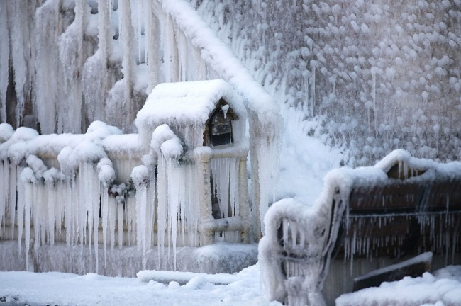 A mailbox and bench are covered with ice near a building which caught on fire, and was doused by firefighters in Plattsmouth, Nebraska, on January 3, 2014. (AP Photo/Nati Harnik)