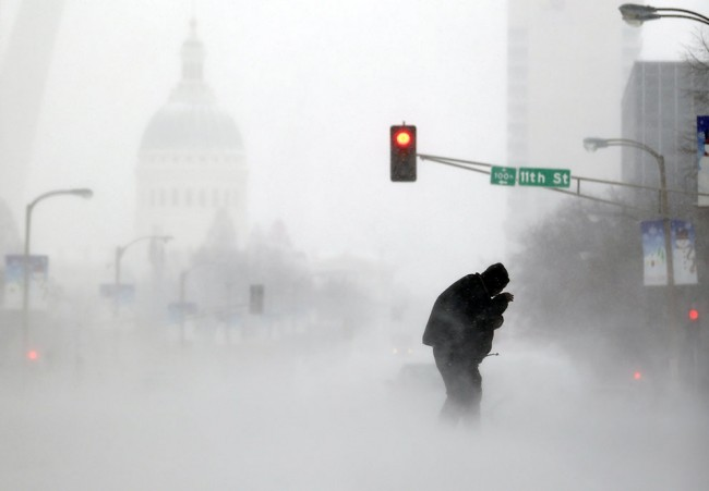 A person struggles to cross a street in blowing and falling snow in St. Louis, on January 5, 2014. (AP Photo/Jeff Roberson)
