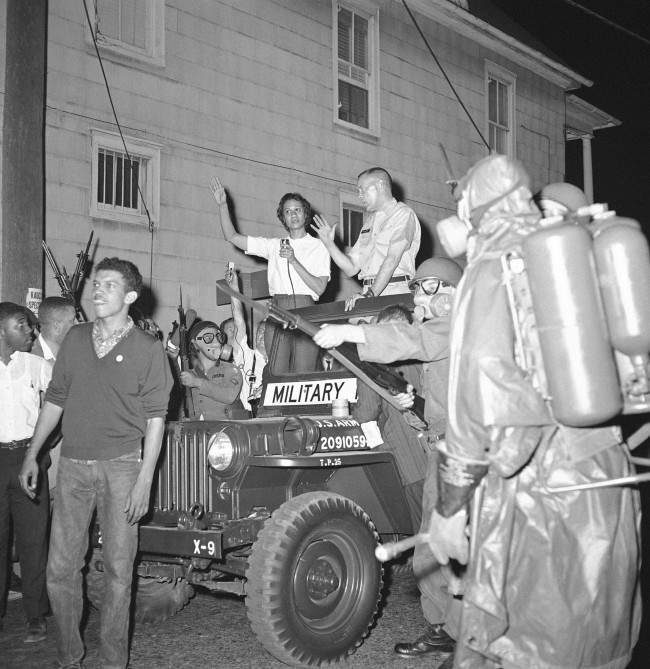Masked National Guardsman with their bayonets held at the ready surround the jeep of Brig. Gen. George Gelson, head of the guard unit, as Stanley Branche, chairman of the Committee for Freedom Now, left, and Mrs. Gloria Richardson, left, stands beside him in Cambridge, Maryland on May 11, 1964. The guard had to disperse a crowd of approximately 300 who tried to march toward the arena where Alabama Gov. George Wallace was speaking.