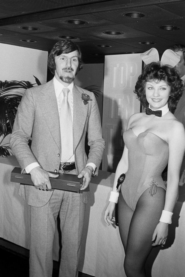 Fashion - Tie Manufacturers Association Tiemen of 1975 - Playboy - London Bunny Girl Carolyn Moore (r) with TV and sports personality Jimmy Hill who is one of the Tie Manufacturers Association Tiemen of 1975.  Date: 23/04/1975