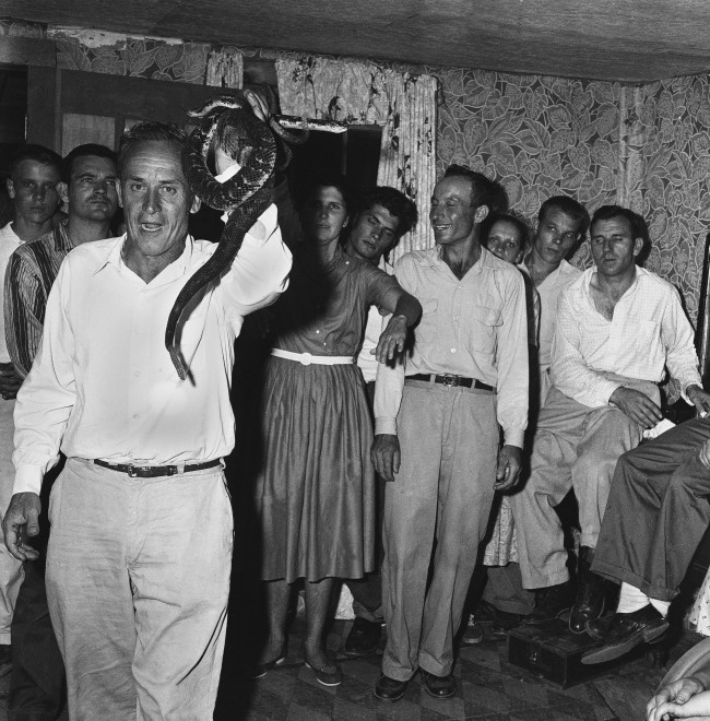 Back in the remote section of the hills southeast of Manchester, Kentucky, Holiness Church meeting was held. James Estep demonstrates his faith by handling four rattle snakes without fear, July 5, 1959. The meeting was held in the home of Forester Asher at a community called Blue Hole on the Clay and Leslie County line.