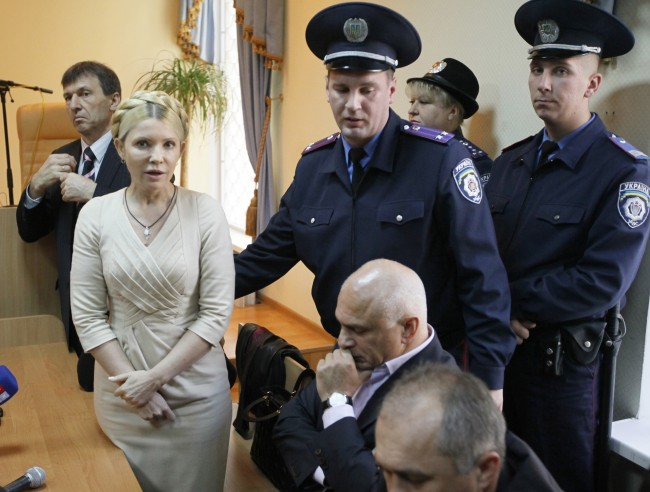 In this Tuesday, Oct. 11, 2011 file photo Police officers lead former Ukrainian Prime Minister Yulia Tymoshenko out of the courtroom after a verdict in her case has been rendered at the Pecherskiy District Court in Kiev, Ukraine. A Kiev court has upheld the conviction and seven-year jail sentence for former Ukrainian Prime Minister Yulia Tymoshenko, condemned as politically motivated by the West. Tymoshenko was found guilty of abuse of office in October and sentenced to prison for overstepping her authority while negotiating a natural gas contract with Russia in 2009.