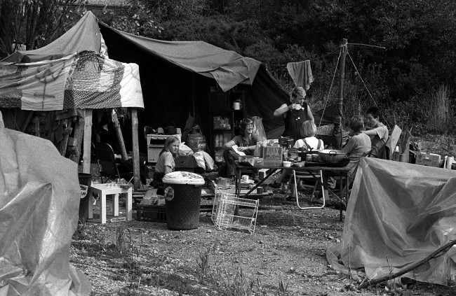 "Greenham Common peace women around a table at their camp at the ""Yellow Gate"" site. Bailiffs moved in to clear women from a small encampment outside 'Green Gate', the entrance closest to the silos where it is planned to site American cruise missiles. Date: 26/08/1983"
