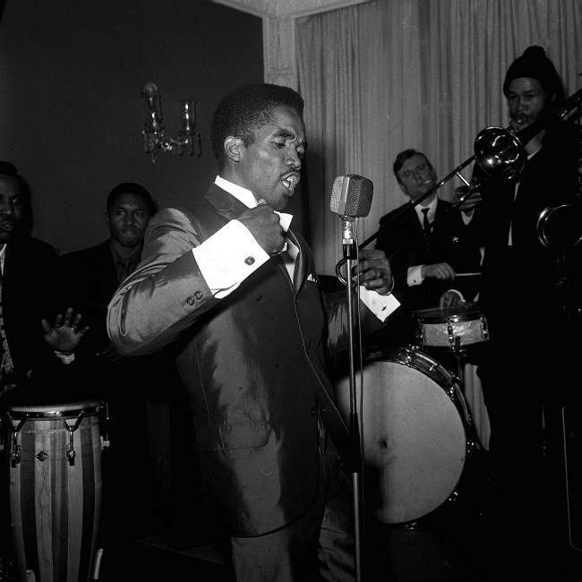 : It's the Blue Beat style as demonstrated by Prince Buster (25) at a reception at the May Fair hotel in London. Blue Beat music is based on a West Indian blues style known as 'Ska Blues'. Buster is here for radio and TV appearances and has brought a Blue Beat hat (a trilby) as gift for Prince Charles. Date: 27/02/1964