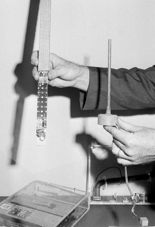 "A State Department security person holds one of the more than 40 microphones found in the American Embassy in Moscow when walls of the building were torn down in April 1964. On display May 19, 1964 at the State Department in Washington are other listening devices uncovered in other American embassies behind the ""Iron Curtain."""