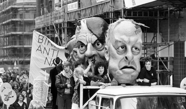 "Carnival heads representing National Front leaders John Tyndall (right) and Martin Webster flanking Adolf Hitler on a lorry in a procession of thousands of demonstrators marching from Trafalgar Square to Victoria Park, Hackney, as part of a ""Carnival Against the Nazis"" organised jointly by the Anti-Nazi League an Rock Against Racism."