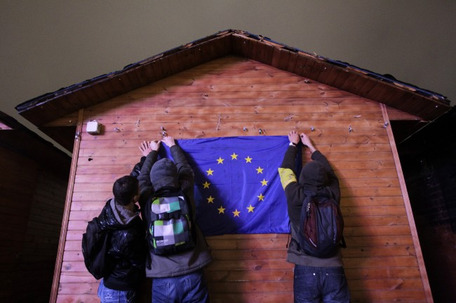 Activists hang an EU flag during a rally in support of Ukraine's integration with the European Union in the center of Kiev, Ukraine, Friday, Nov. 22, 2013.
