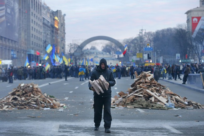 A protester collects firewood for heating in downtown Kiev, Ukraine, early Wednesday, Dec. 4, 2013. Ukraine's opposition failed to force out the government with a parliamentary no-confidence vote Tuesday, leaving political tensions unresolved and a potential standoff between protesters and the country's leaders looming.