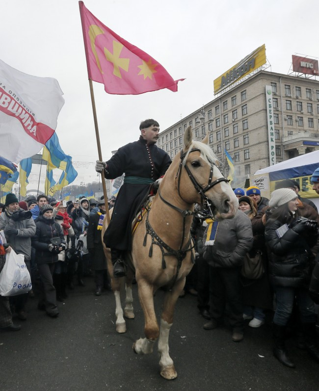 A man dressed as a Cossack on a horse parades through the street during a Pro-European Union rally in Independence Square, Kiev, Ukraine, Sunday, Dec. 8, 2013. The third week of protests continue Sunday with an estimated 200,000 Ukrainians occupying central Kiev to denounce President Viktor Yanukovych's decision to turn away from Europe and align this ex-Soviet republic with Russia.