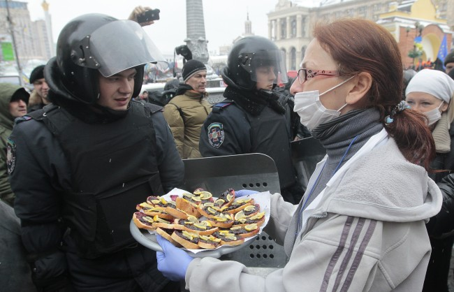 A Pro-European Union activist tries to give food to riot police officers preparing to block the Independence Square in KIev, Ukraine, Monday, Dec. 9, 2013. The policemen, wearing helmets and holding shields, formed a chain across Kiev's main street outside the city building. Organizers called on protesters to vacate the city hall and the other building which the opposition had used as its headquarters.