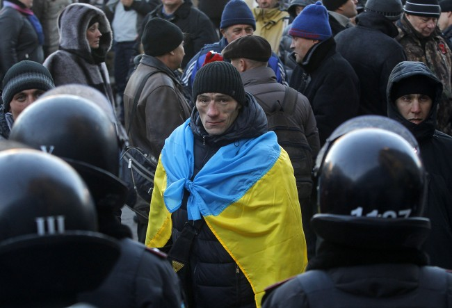 A supporter of Yanukovych's party of Regions wearing a Ukrainian national flag stands in front of police line during their rally next to pro-European Union's protesters at Independence Square in Kiev, Ukraine, Saturday, Dec. 14, 2013. The opposition has called for a vast turnout to a rally on Sunday. Rallies on the previous two Sundays drew hundreds of thousands of protesters. That same day, Yanukovych's Party of Regions has called for a pro-government demonstration that it claims will bring 200,000 people to Kiev.