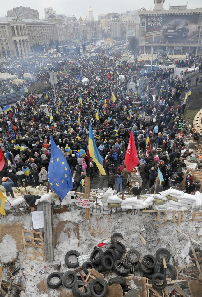 Barricades made of snow, tyres, wood and wire, foreground, protect a pro-European Union mass rally from riot police in Independent square in Kiev, Ukraine, Sunday, Dec. 15, 2013. About 200,000 anti-government demonstrators converged on the central square of Ukraine's capital today, a dramatic demonstration that the opposition's morale remains strong after nearly four weeks of daily protests.