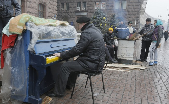 An activist plays the piano for Pro-European Union supporters which warm themselves near a bonfire in the city main street of Khreschatyk in Kiev Ukraine, Monday, Dec. 16, 2013. Ukraine's opposition appears confident and shows no sign of relenting in its standoff with the government. The government has made some gestures toward the opposition, rejected some of its main demands and is opaque on another.