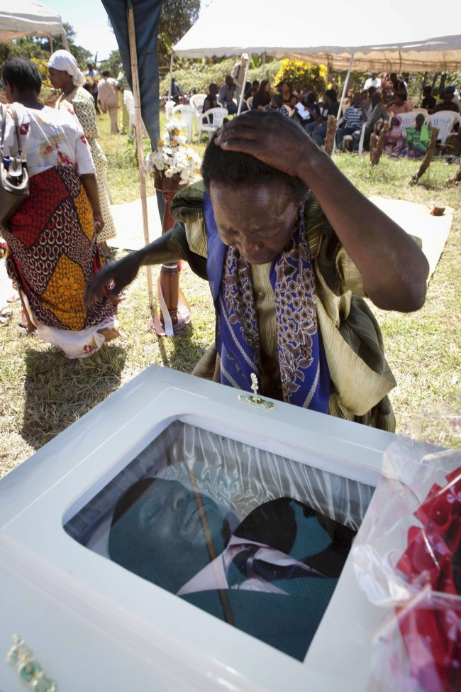 "In this Friday, Jan. 28, 2011 file photo, a woman grieves at the coffin of gay activist David Kato in Mukono, Uganda. As a prominent Ugandan gay rights activist, his picture was published by an anti-gay newspaper next to the words ""Hang Them."" He was killed on Wednesday, Jan. 26, 2011. Police said Thursday his sexual orientation had nothing to do with the killing and that one ""robber"" had been arrested. Uganda has been under scrutiny by international gay-rights groups since 2009, when a lawmaker proposed a bill that would mandate the death penalty for some gay acts."