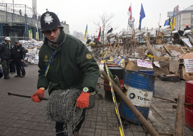 "pro-European Union activist unwinds barbed wire to reinforce the barricades around Independence Square in case the tent camp is stormed by police, in Kiev, Ukraine, Wednesday, Dec. 18, 2013. Russian President Vladimir Putin and Ukrainian President Viktor Yanukovych both pledged Tuesday, Dec. 17, 2013 to boost economic and trade ties to expand the ""strategic partnership"" between the two neighbors."