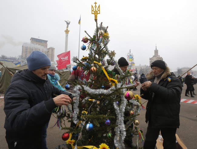 Pro-European Union activists decorate a Christmas tree during a rally in Independence Square in Kiev, Ukraine, Friday, Dec. 20, 2013. Anti-government demonstrators continued to occupy Kiev's Independence Square, expressing their anger over a bailout Ukrainian President Viktor Yanukovych negotiated with Russia earlier this week.