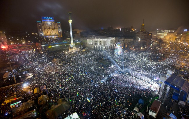 Pro-European Union activists hold light as they sing the Ukrainian national anthem, celebrating the New Year in the Ukrainian capital Kiev's main square early Wednesday, Jan. 1, 2014. At least 100,000 Ukrainians sang the country's national anthem together at the square on New Year's Eve in a sign of support for integration with Europe. Opposition leaders had called on Ukrainians to come to Kiev's Maidan on the New Year's Eve and sing the national anthem in an act of defiance and what they expected could be the record-breaking live singing of an anthem.