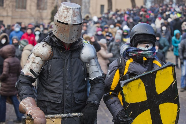 Protesters clad in improvised protective gear prepare for a clash with police in central Kiev, Ukraine, Monday, Jan. 20, 2014. After a night of vicious streets battles, anti-government protesters and police clashed anew Monday in the Ukrainian capital Kiev. (